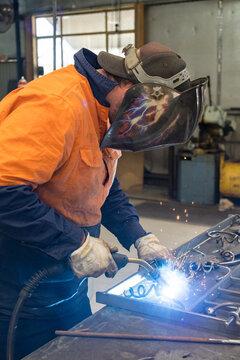 A tradesman wearing high vis clothing welding steel on a workbench