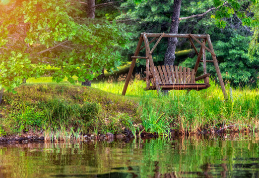 Wooden swing seat by a lake at sunset