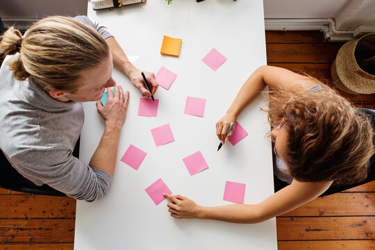 Two people working on a planning session from above
