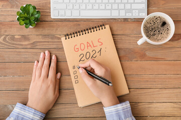 Fototapeta Woman making to-do list on 2021 year at table