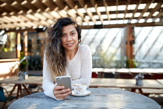 Young middle eastern woman enjoying time on phone at cafe