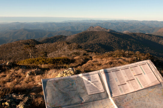 A map being held with mountain ranges in the background.
