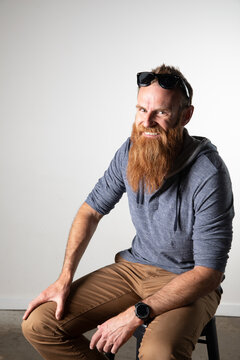 Man with long beard and sunglasses seated and smiling