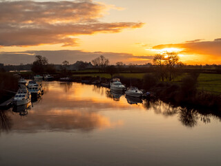 Beautiful sunset sky reflected in the calm water of the River Ouse with moored boats near York, England