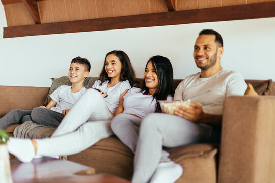 Latin family enjoying the day together at home watching tv on the couch wearing pajamas