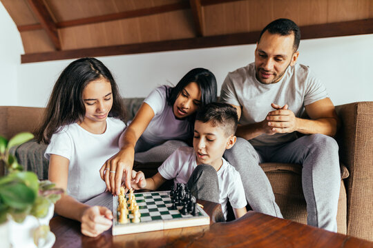 Family playing chess together in the living room