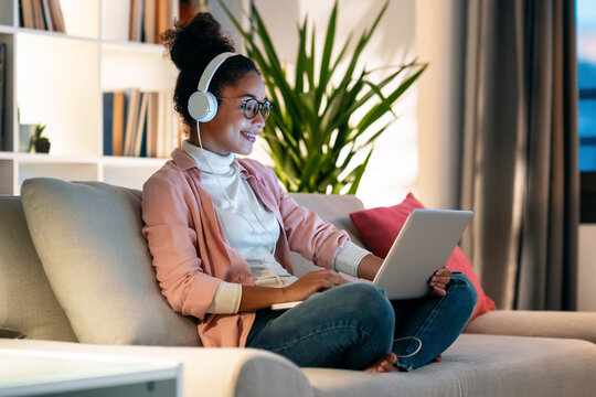 Beautiful young entrepreneur woman working with laptop while listening music with headphones sitting on couch in the office.