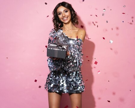 Beautiful happy woman wearing sparkle dress with gift box at celebration party with confetti falling everywhere on her