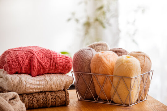 Cozy knitted sweaters with balls of yarn in the living room