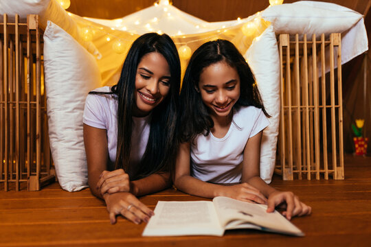 Young latin mother and her daughter reading book at home