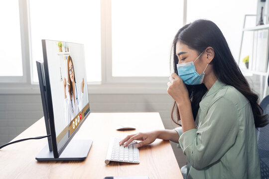 Asian woman patient in an online video call with a professional doctor examining diagnosing disease viruses giving medical health advice for wellbeing, using computer laptop, wearing surgical facemask