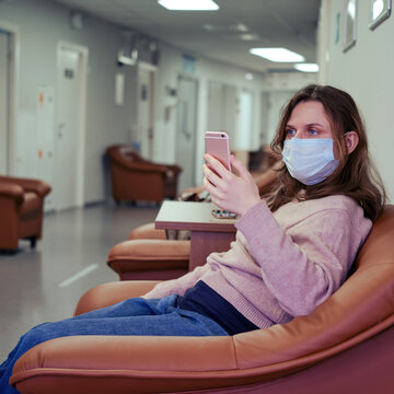 A patient in the clinic corridor is watching an appointment with a doctor online on their phone