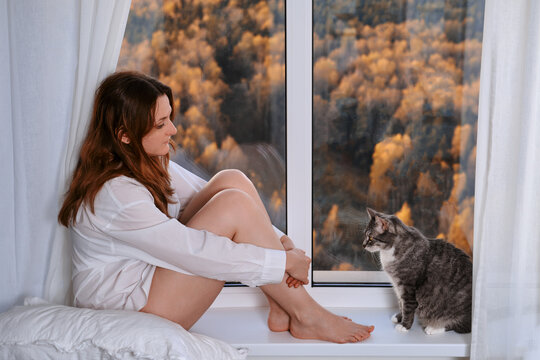 A red-haired woman sits at the autumn window and looks at the cat. Sad autumn nature and home comfort