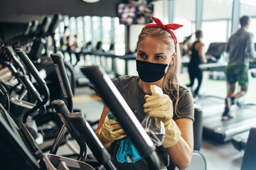 Young female worker disinfecting cleaning and weeping expensive fitness gym equipment with alcohol sprayer and cloth. Coronavirus global world pandemic and health protection safety measures.