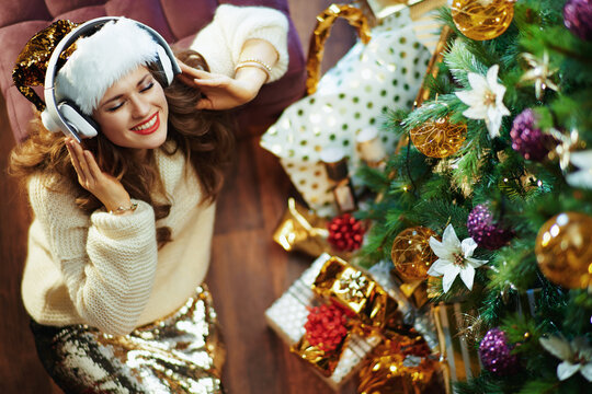 woman listening to music near Christmas tree and gift boxes