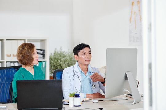 Team of Vietnamese medical workers watching video on computer on new ways of coronavirus treatment