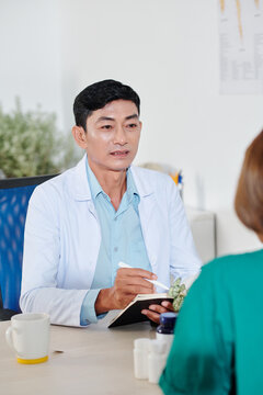 Mature serious chief physician talking to colleague and writing in notebook