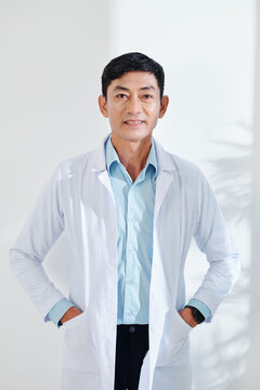 Portrait of smiling mature Asian general practitioner in labcoat looking at camera