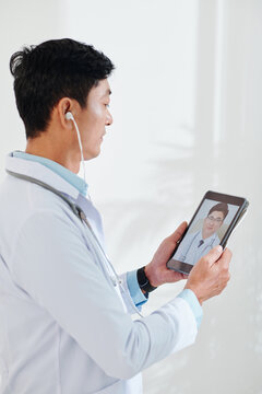 Serious mature general practitioner video calling colleagues to discuss difficult case