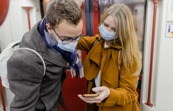 People using phone in train wearing covid-19 face mask