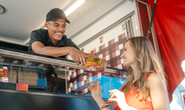 Cook in a food truck handing tasty burger over to woman customer