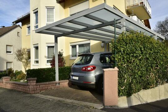 Neuer grauer Carport aus beschichtetem Aluminium mit Pult-Glasdach an einem Wohnhaus