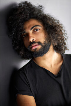 close-up portrait of curly indian male having deep look, handsome guy in casual black t-shirt is in contemplation