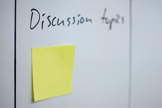 Yellow sticker on the whiteboard with discussion topics label