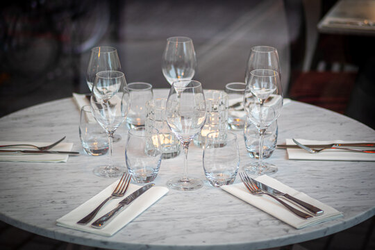 Empty round restaurant table with wine glasses and candles