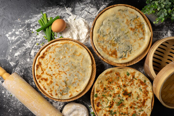 Three types of classic unleavened wheat flatbread with herbs and cheese made from flour, eggs, onions and water. An assortment of freshly baked bakery products.