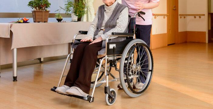 老人福祉施設 高齢者が座る車イスを押す介護スタッフ
