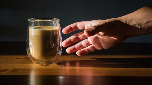 Male holds hand pglass cup with coffee on dark background