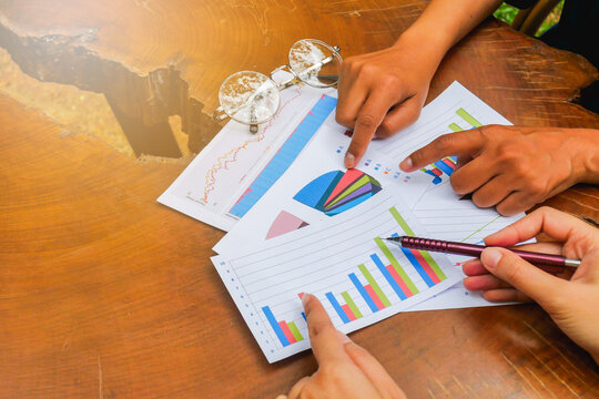 Cropped Image Of People Discussing Over Graphs On Table