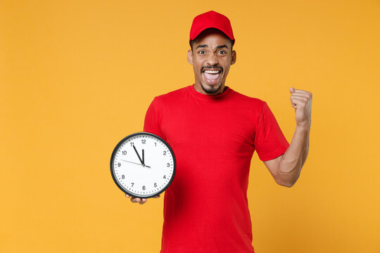Delivery employee african man in red cap blank print t-shirt uniform workwear work courier service during quarantine coronavirus covid-19 virus concept hold clock isolated on yellow background studio.