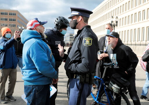 Michigan State Police separate a counter protestor from U.S. President Donald Trump's supporters as the Board of State Canvassers meet to certify the results of the election in Lansing