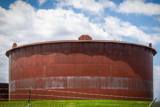 Giant rusty oil tank in tank farm in Cushing Oklahoma behind barbed wire fence with pretty blue sky background