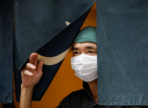 Sixty-year-old Yashiro Haga rolls a shop curtain at the entrance of his ramen noodle shop 'Shirohachi', amid the coronavirus disease (COVID-19) outbreak, in Tokyo