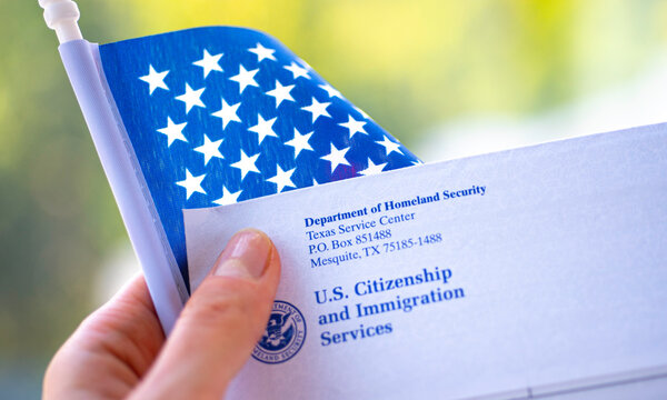 Washington, DC, USA - September, 16, 2019: Letter (Envelope) from USCIS ans flag of USA in hand on green blurred background. Close up view.