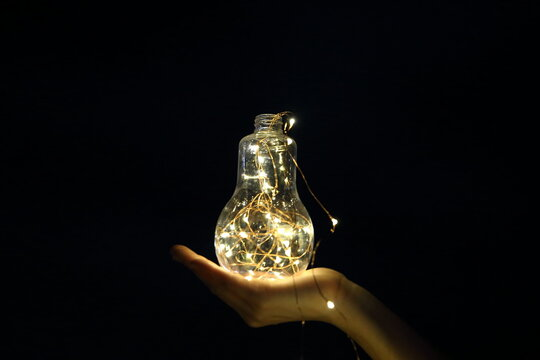 Cropped Hand Of Woman Holding Illuminated Light Bulb Against Black Background