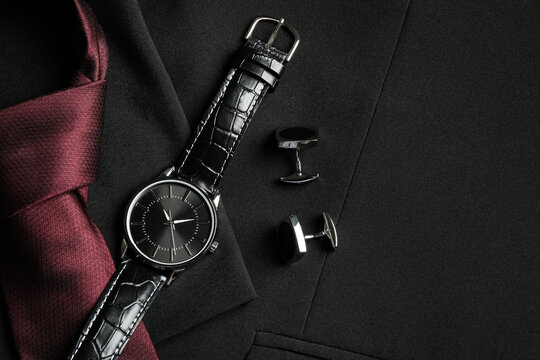 Flat lay composition with luxury wrist watch on black jacket