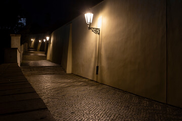 sidewalk with cobblestones for pedestrians and light from street lights in the center of Prague at night Fotomurales
