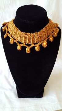 Handmade rose-gold color, a crocheted necklace with gold color matching beads. The piece sits on a black jewelry stand.