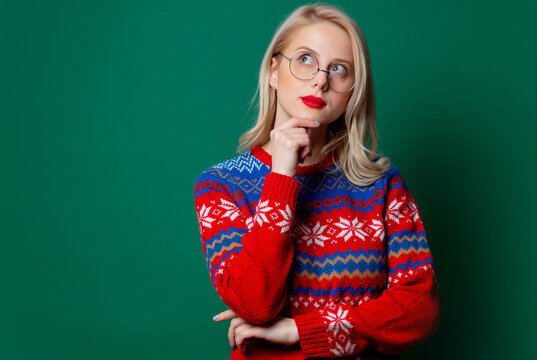 Beautiful woman in Christmas sweater and glasses on green background