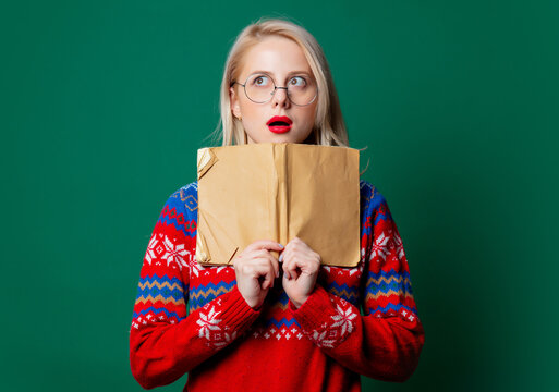 Beautiful woman in Christmas sweater with a book