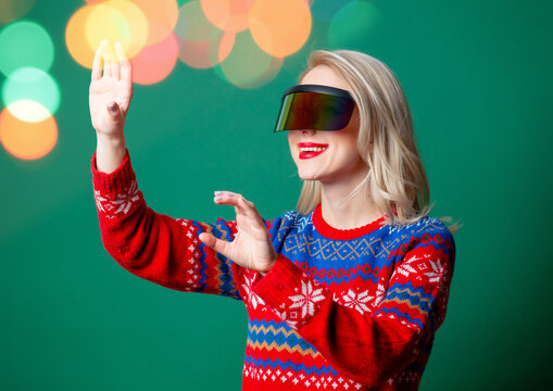 Beautiful woman in Christmas sweater and VR glasses on green backgrou