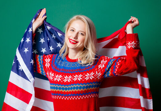 Beautiful woman in Christmas sweater and USA flag on green background