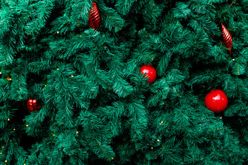 Wall Mural - Closeup of Festively Decorated Outdoor Christmas tree with bright red balls on blurred sparkling fairy background