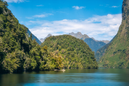 Close up view of the incredible alpine scenery at Doubtful Sound which includes a sphere-shaped mountain covered in rainforest as most of the other mountain range in the fjord in New Zealand.
