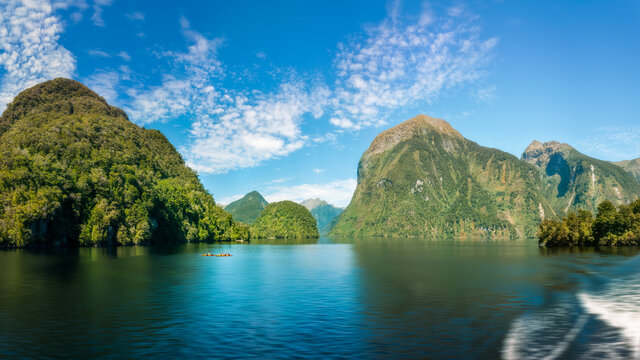Awesome panoramic views from a cruise boat with alpine scenery with towering mountains and ice-carved valleys and rainforests covering the steep sides at Doubtful Sound in New Zealand, South Island.
