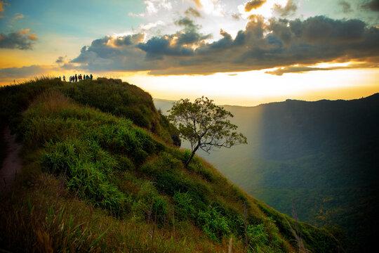 tourist on mountain top of phu tubberk thailand against beautiful sun light